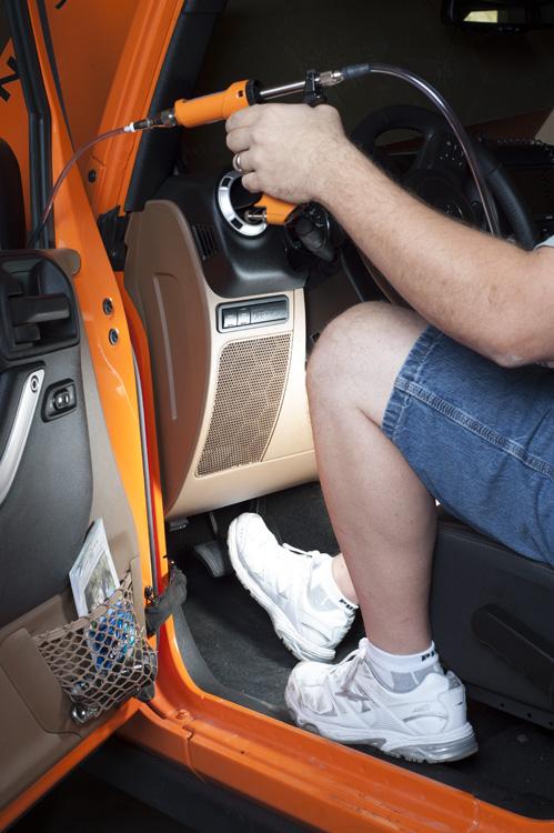 Man steps on brake pedal while using XL brake fluid flush hose and reverse bleeder tool