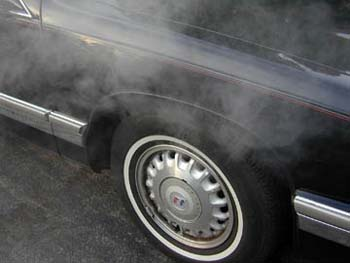 Car tire with smoke coming from brakes