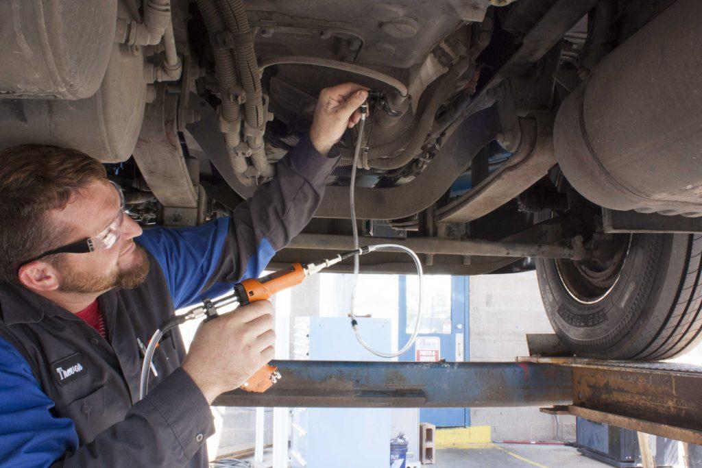 Auto mechanic uses car brake bleeding kit on a diesel truck