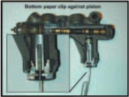 Bottom paper clip against piston
